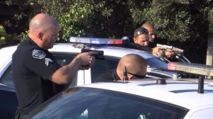 Torrance police officers point their weapons at the occupants of a vehicle after a pursuit on April 10, 2016. (Credit: SHP)
