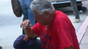 Raul Rodriguez Jr. sits down after he said he was pepper-sprayed at a Trump-related rally in Anaheim on April 26, 2016. (Credit: KTLA)