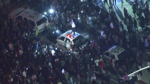 Someone jumps on a police car at an anti-Trump protest outside a campaign rally in Costa Mesa on April 28, 2016. (Credit: KTLA)