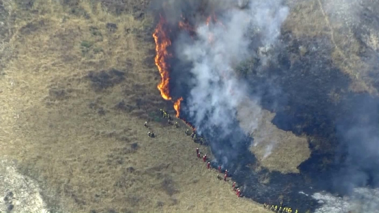 Firefighters seek to contain a brush fire burning above Lake View Terrace on May 23, 2016. (Credit: KTLA)