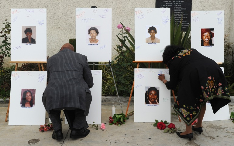 """Reverend Dr. Kelvin Calloway, left, leaves a message on photographs set up as a memorial for 10 of the victims of the serial killer dubbed the """"Grim Sleeper"""" in Los Angeles on Aug. 10, 2010. (Credit: MARK RALSTON/AFP/Getty Images)"""