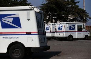 U.S. Postal Service mail vehicles sit in a parking lot at a mail distribution center on Feb. 18, 2015, in San Francisco. (Credit: Justin Sullivan/Getty Images)