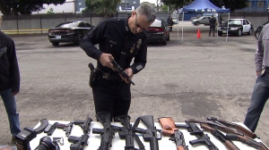 A police official examines a firearm at an LAPD gun buyback event on May 7, 2016. (Credit: KTLA)