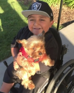Juan Hernandez, 10, and his service dog Buddy are seen in a photo provided by his family.