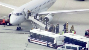 Passengers are led off a American Eagle plane at LAX on May 24, 2016. (Credit: KTLA)