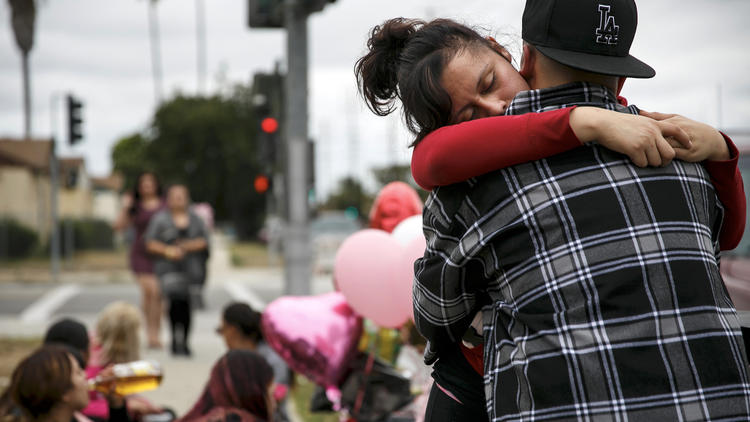Miriam Ambriz gets an embrace as she mourns the loss of her sister, Cynthia Ambriz, 19, who was shot and killed while walking in Carson on June 11, 2016. (Credit: Marcus Yam/Los Angeles Times)