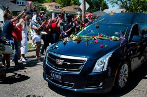 The hearse carrying boxing legend Muhammad Ali drives past his childhood home where mourners throw flowers as they pay their respects on June 10, 2016, in Louisville, Kentucky. (Credit: JIM WATSON/AFP/Getty Images)