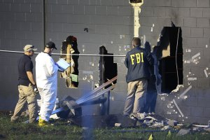 FBI agents investigate near the damaged rear wall of the Pulse nightclub where a gunman killed at least 50 people on June 12, 2016, in Orlando, Florida. (Credit: Joe Raedle/Getty Images)