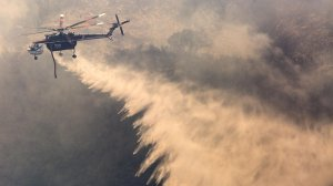 A helicopter drops water on the Scherpa Fire as it consumes heavy brush along Refigio Road in Santa Barbara County on June 16, 2016. (Credit: Brian van der Brug / Los Angeles Times)