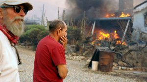 Residents Sal Blanco, left, and Nelson Hernandez watch a neighbor's house burn along Kelso Valley Road east of Lake Isabella during the Esrkine fire Friday. (Credit: Wally Skalij / Los Angeles Times)