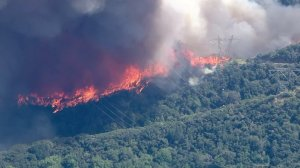 Flames burned up to the base of transmission towers in the San Gabriel Mountains on June 20, 2016. (Credit: KTLA)