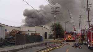A dark plume of smoke is seen emanating from a commercial fire in Maywood on June 14, 2016. (Credit: KTLA)