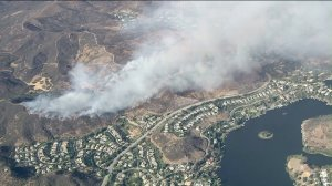 Plumes of smoke rise above Lake Sherwood on July 13, 2016, during a brush fire that burned 78 acres. (Credit: KTLA)