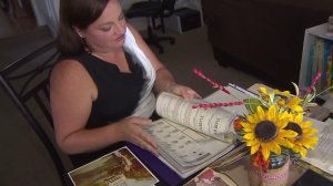 Corinne McIntire looks through old documents pertaining to her mother's case on July 27, 2016. (Credit: KTLA)