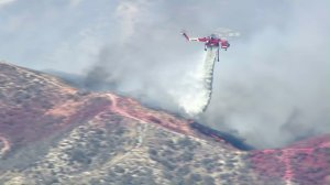 A helicopter drops water on a brush fire in Santa Clarita on July 22, 2016. (Credit: KTLA)