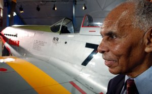 Captain Roscoe C. Brown (RET) stands next to the actual P-51 Mustang he flew as a member of the Tuskegee Airmen during World War II. (Credit: Stephen Chernin/Getty Images)