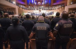"""Police join hands during the singing of """"The Battle Hymn of the Republic"""" during an interfaith memorial service for the victims of the Dallas police shooting at the Morton H. Meyerson Symphony Center on July 12, 2016 in Dallas, Texas. (Credit: MANDEL NGAN/AFP/Getty Images)"""