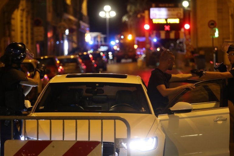 Police officers carry out checks on vehicles in the center of French Riviera town of Nice, after a vehicle drove into a crowd watching a fireworks display on July 14, 2016. (Credit: VALERY HACHE/AFP/Getty Images)