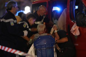 Rescue workers help an injured woman to get in a ambulance on July 15, 2016, after a truck drove into a crowd watching a fireworks display in the French Riviera town of Nice. (Credit: VALERY HACHE/AFP/Getty Images)