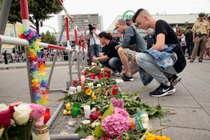 People lay flowers and candles near the crime scene outside the OEZ shopping center the day after a shooting spree left nine victims dead on July 23, 2016 in Munich, Germany. (Photo by Johannes Simon/Getty Images)