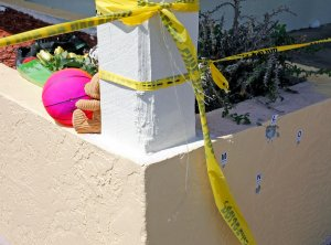 A small memorial begins near where bullet holes are marked outside of Club Blu where two people were killed and at least 15 wounded on July 25, 2016, in Fort Myers, Florida.  (Credit: Mike Carlson/Getty Images)