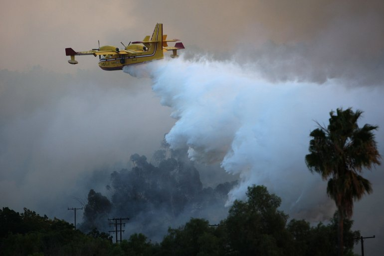 A firefighting Super Scooper airtanker drops water over the Brea Fire on Nov. 15, 2008, near Yorba Linda. (Credit: David McNew/Getty Images)