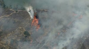 A helicopter makes a water drop on a brush fire burning in the Hollywood Hills on July 19, 2016. (Credit: KTLA)
