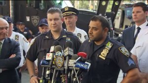 NYPD Officer Peter Cybulski, left, and Sgt. Hameed Armani, right, talk about the terrifying moment a suspected bomb was thrown in their patrol vehicle in Times Square on July 20, 2016. (Credit: WPIX)