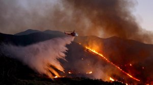 A helicopter drops water on the fast-growing Sand Fire east of Santa Clarita. (Credit: Francine Orr / Los Angeles Times)