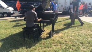 """People gathered at a memorial outside the Dallas Police Department were taken by surprise on Sunday when a man pulled up on a bicycle, a piano in tow. Without saying a word, the gentleman began playing a rendition of John Lennon's """"Imagine."""" (Credit: @liz.rd/Instagram)"""