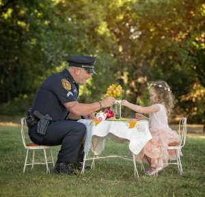 Corporal Patrick Ray sits down at a tea party with 2-year-old Bexley one year after saving her life. (Credit: Chelle Cates Photography)