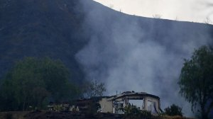 A smoldering home off the 26700 block of Iron Canyon Road on Sunday morning. (Credit: Francine Orr / Los Angeles Times)