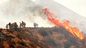 Heat from flames push firefighters back as they monitor a flare up in brush along Soledad Canyon Road near Acton on Monday. (Credit: Al Seib/Los Angeles Times)
