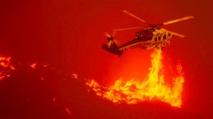 A firefighting helicopter hovers close to the flames from the Sand fire as it burns out of control along Soledad Canyon Road near Acton on Sunday. (Credit: Luis Sinco/Los Angeles Times)