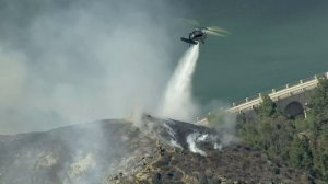 A helicopter drops water on a brush fire burning in the Hollywood Hills on July 19, 2016. (Credit: KTLA)