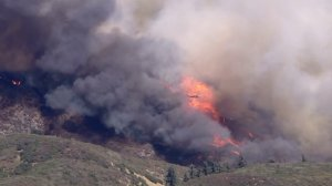 A helicopter makes a water drop on the fast-moving Blue Cut Fire in the Cajon Pass. (Credit: KTLA)