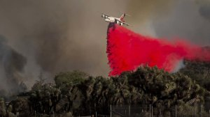 An air tanker drops fire retardant near homes as the Blue Cut fire burns out of control on both sides of Highway 138 in Summit Valley, California. (Credit: Gina Ferazzi / Los Angeles Times)