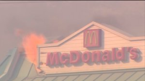 A water drop was made on a McDonald's restaurant off the 15 Freeway as flames ignited the roof on Aug. 16, 2016. (Credit: KTLA)