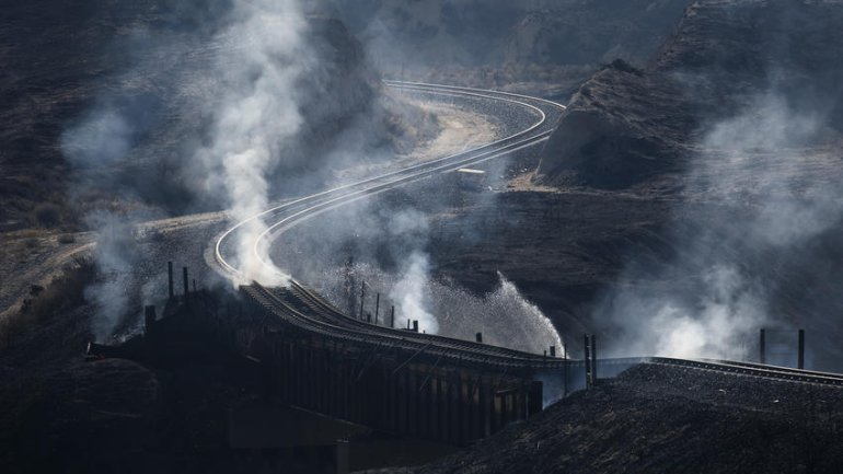 Smoke rises from beneath railroad tracks damaged by the Blue Cut Fire. (Credit: Marcus Yam / Los Angeles Times)