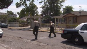 Los Angeles County Sheriff's Department officials investigate the death of a 71-year-old man in Compton on Aug. 27, 2016. (Credit: KTLA)