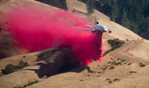 A plane drops fire retardant while battling the Soberanes Fire in Carmel Highlands on July 23, 2016. (Credit: NOAH BERGER/AFP/Getty Images)