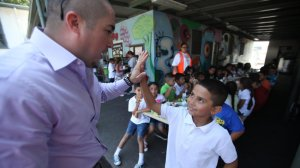 Juan Carlos Rodriguez, left, Title I coordinator, gives a high-five to second-grader Armando Rodriguez, 7, during lunch on the first day of school at Hadden Elementary School in Pacoima in August 2013. (Credit: Francine Orr / Los Angeles Times)