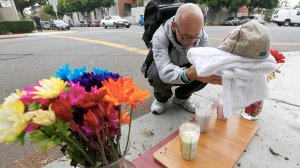 Neighborhood resident Fred Purdue adds a baseball cap, baby blanket and votive candles to a makeshift memorial at the intersection of 9th Street and Locust Avenue in Long Beach, where a a mother and her daughter were shot and killed on Saturday night. (Credit: Luis Sinco / Los Angeles Times)