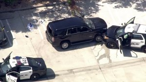 A GMV Yukon and a police SUV both have bullet holes in their windshield after a shooting in Lawndale on Aug. 2, 2016. (Credit: KTLA)