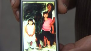 Patricia Santiago Venture of Placentia and her daughters are shown in a photo held up by a mourner on Aug. 21, 2016, at the scene where they were killed the previous night. (Credit: KTLA)