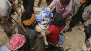 Syrians carry the body of child after pulling it out from under the rubble of a building following bombardment in the northern Syrian city of Aleppo on Sept. 23, 2016. (Credit: Ameer Alhalbi/AFP/Getty Images)