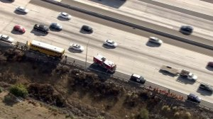 A school bus that caught fire is at left, and students that were moved of the bus are at right along the 210 Freeway in Lake View Terrace on Sept. 29, 2016. (Credit: KTLA)