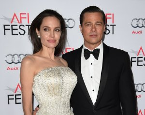 """Writer-director-producer-actress Angelina Jolie Pitt and actor-producer Brad Pitt arrive for the opening night gala premiere of Universal Pictures' """"By the Sea"""" at the TCL Chinese Theatre in Hollywood on Nov. 5, 2015. (Credit: MARK RALSTON/AFP/Getty Images)"""