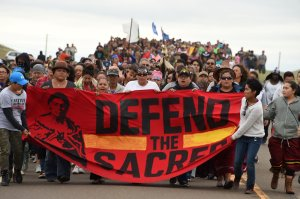 Native Americans march to the site of a sacred burial ground that was disturbed by bulldozers building the Dakota Access Pipeline (DAPL), near the encampment where hundreds of people have gathered to join the Standing Rock Sioux Tribe's protest of the oil pipeline slated to cross the nearby Missouri River, Sept. 4, 2016, near Cannon Ball, North Dakota. (Credit: ROBYN BECK/AFP/Getty Images)