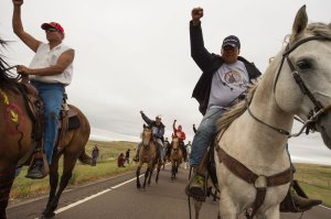 Native Americans ride with raised fists to a sacred burial ground that was disturbed by bulldozers building the Dakota Access Pipeline, near the encampment where hundreds of people have gathered to join the Standing Rock Sioux Tribe's protest of the oil pipeline slated to cross the nearby Missouri River, Sept. 4, 2016 near Cannon Ball, North Dakota. (Credit: ROBYN BECK/AFP/Getty Images)